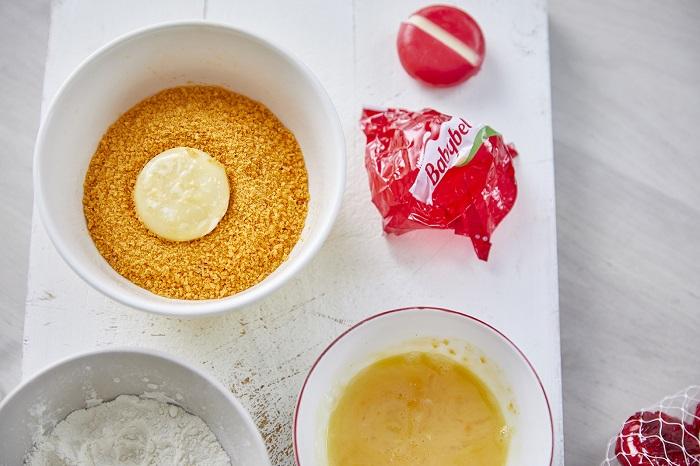 """מצרסלט איכרים עם שניצלוני בייבי בל כים: 1 ראש לבבות חסה, עלים בהירים 10-15 עגבניות שרי, בכל צבע שאוהבים 1/2 בצל סגול, קלוף 2 מלפפונים 10-15 זיתים שחורים או זיתים, ללא גלעין לשניצלוני ביי בל: 1 מארז גבינת בייבי בל 3/4 כוס קמח 2 ביצים M 3/4 כוס פירורי פנקו (או פירורי לחם) שמן לטיגון לרוטב: 3 כפות שמן זית 3 כפות מיץ לימון 1/2 כפית מלח 1/2 כפית חומץ בלסמי 1 כפית מייפל אופן הכנה: - חותכים את החסה לרצועות בעובי 3 ס""""מ וחוצים את העגבניות לחצי. - פורסים את הבצל לפרוסות דקות מאוד ואת המלפפונים לפרוסות אלכסוניות. - מערבבים את כל הירקות בקערה גדולה. - מניחים 3 קערות על השיש. באחת שמים קמח, בשנייה ביצים טרופות ובשלישית פירורי לחם. - מסירים את העטיפה האדומה מהגבינה ומקמחים בקמח. מעבירים לביצה ומשם לפירורי הלחם. חוזרים שוב לביצים ואז שום לקמח. מכינים בצורה הזו את כל הבייבי בל ומניחים במקרר עד שמחממים את השמן. - מחממים שמן בגובה 3-4 ס""""מ בסיר קטן או במחבת ומטגנים את שניצלוני הגבינה עד הזהבה משני הצדדים. - מניחים את השניצלונים החמים על הסלט. - מערבבים את מצרכי הרוטב ומזלפים על הסלט. אוכלים מיד. הערות ושדרוגים - אפשר להגיש את השניצלונים האלה גם לארוחת ערב לצד חביתה, סלט ירקות קצוץ דק או בתוך לחמנייה ממש כמו שניצל קטן. - רוצים להכין את הסלט קודם? מכינים את הרוטב בנפרד, הירקות החתוכים מעורבבים בקערה ואת הבייבי בל כבר עטוף בפירורי לחם. לפני שהאורחים מגיעים רק מטגנים את השניצלונים, מניחים מעל הסלט ומזלפים רוטב. - אפשר כמובן להחליף כל ירק בסלט לפי הטעם האישי שלכם. גמבה למשל תעבוד כאן מעולה. - רוצים לשדרג? חותכים פיתה למשולשים ומברישים בשמן זית עם קצת מלח. אופים בתנור עד הזהבה ומניחים מעל הסלט כמו קרוטונים."""